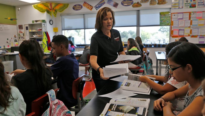 Hermosa Middle School science teacher Cindy Colomb passes out materials to her students on Aug. 25.