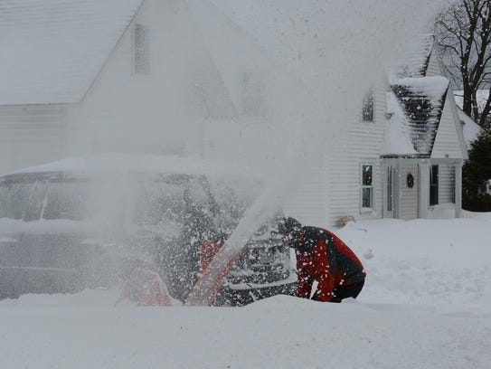 Driver using snow thrower to dig out a vehicle covered