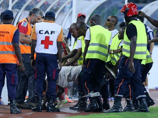 A missile is thrown next to an Equatorial Guinea supporter who invaded the pitch during their African Cup of Nations semifinal soccer match with Ghana at Estadio De Malabo, Equatorial Guinea, Thursday Feb. 5, 2015.  With riot police protecting the players from incensed rival fans and using tear gas to disperse troublemakers in the crowd, Ghana advanced to the African Cup of Nations final with a 3-0 win over host Equatorial Guinea on Thursday. (AP Photo/Sunday Alamba)