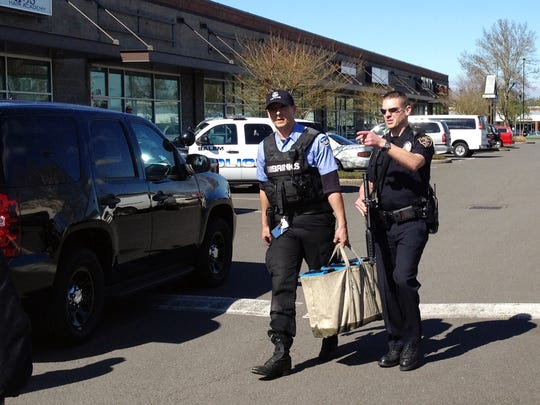 An armed Brinks guard, left, is escorted to safety Tuesday by Keizer police following a robbery at a shopping center in Keizer.