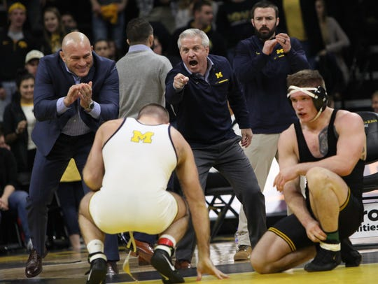 The Michigan coaching staff celebrates as Iowa's Cash