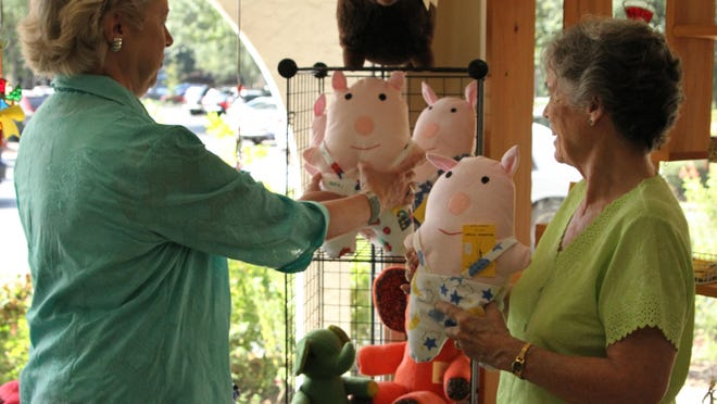 Artisans' Guild Gallery staff can be seen in this 2010 file photo displaying personalized stuffed pigs that served as a popular gift for many decades. The gallery is open to the public with safety measures in place.
