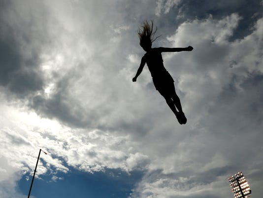 A Kansas cheerleader is silhouetted against storm clouds during the first half of an NCAA college football game against Central Michigan Saturday, Sept. 20, 2014, in Lawrence, Kan. (AP Photo/Charlie Riedel)