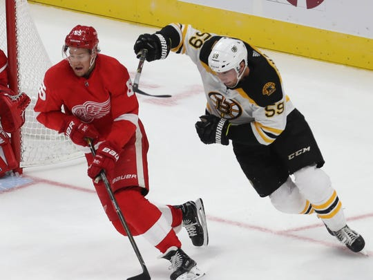 Detroit Red Wings' Danny DeKeyser moves the puck against the Boston Bruins' Tim Schaller in the third period Sept. 23, 2017 at Little Caesars Arena in Detroit.