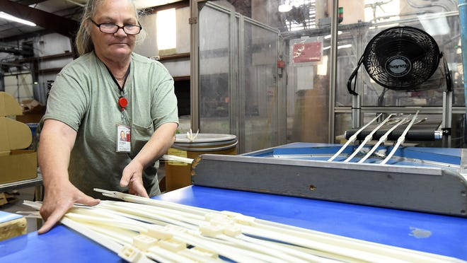 Glenda Fuller, parts handler at Micro Plastics Inc., in Flippin, runs an extruder machine that produces plastic handcuffs. The initial response from the law enforcement community to the one-use plastic restraint has been positive.