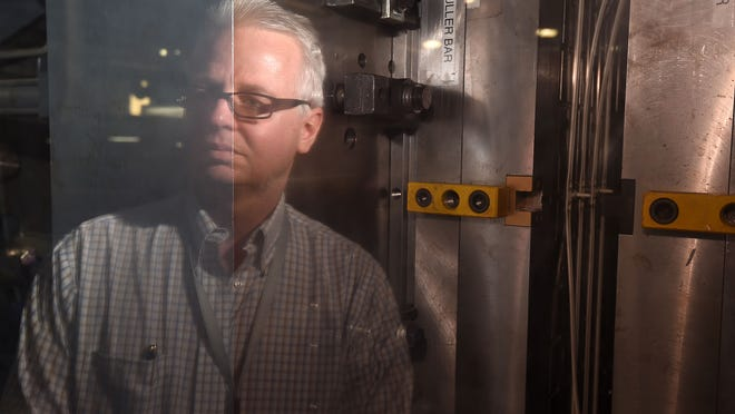 In this file photo, Micro Plastics Inc. President Tom Hill watches as an extruder machine produces plastic handcuffs at the company's Flippin plant. The company has been acquired by Essentra plc, a UK-based global supplier of essential components, according a news release provided Wednesday.