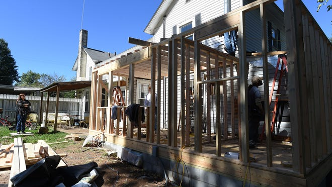 Gamma House director Natalie Slusser (left) watches as members of the Twin Lakes Homebuilders Association work on a new addition to the house.