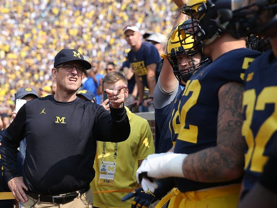Michigan Wolverines coach Jim Harbaugh leads his team