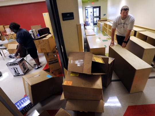 Thomas Landis wheels a cabinet into Long Early Learning Center Wednesday, July 26, 2017, as Celeste Cooper sorts and unpacks boxes in one of the rooms. Teachers and staff spent the day organizing and registering students Wednesday.