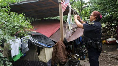 Cincinnati police officer Lisa Johnson takes photos at an abandoned homeless camp in Queensgate. Rather than raiding the camp, police spent months working with social workers to convince residents that it was in their best interests to find other shelter.