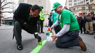 Wilmington Mayor Dennis P. Williams (left) helps paint the green line for the Wilmington St. Patrick's Day parade last year.