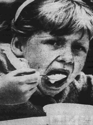 A child eats cereal at the 1961 Cereal City Festival, as covered by the Enquirer and News.