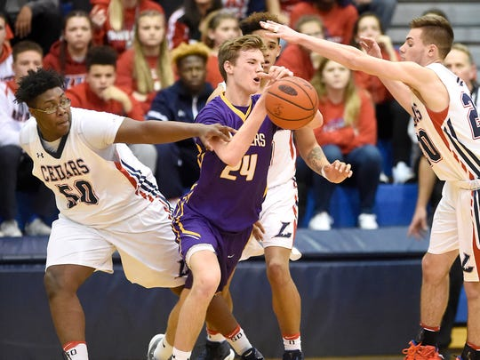 Lebanon's Khalique Washington, left, and Camryn Shaak work to strip the ball from Lancaster Catholic's Danny Bomberger.