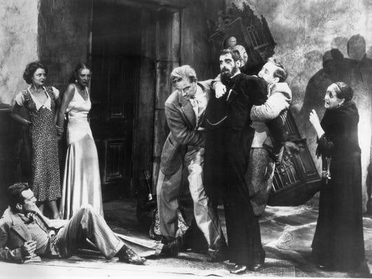 "Melvyn Douglas (from left), Lillian Bond, Gloria Stuart, Raymond Massey, Boris Karloff,  Charles Laughton  and Eva Moore in a scene from ""The Old Dark House."""