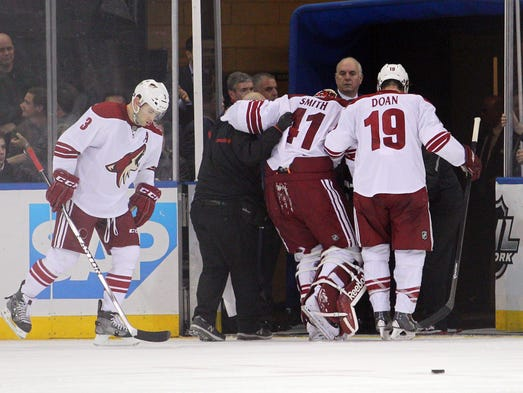 Mar 24, 2014; Phoenix Coyotes goalie Mike Smith (41) is helped off the ice by a trainer and Coyotes right wing Shane Doan (19) after an injury during the third period of a game against the New York Rangers at Madison Square Garden. The Rangers defeated the Coyotes 4-3 in overtime.