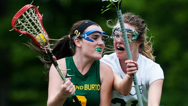 Rice's Caitlin Hester (21) guards Burr and Burton's Ryder Ferrone (2) during a high school girls lacrosse game Saturday. The Bulldogs won 14-9 to seal the top seed for the Division I playoffs.