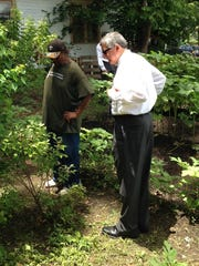 Don Bullock, gardener for the North Alexandria Community Garden, points out a blueberry bush to Lt. Gov. Jay Dardenne during a visit to the garden Tuesday.