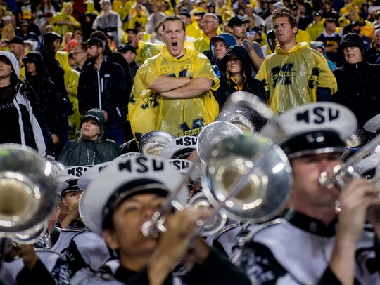A Michigan fan yawns while the MSU band plays late