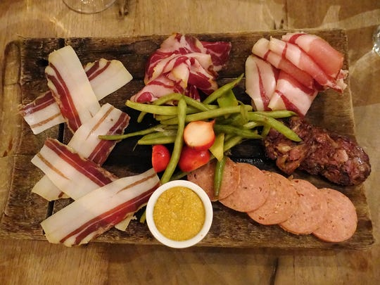 UB charcuterie platter with (clockwise, from left) tessa, coppa, lonza, beef terrine, summer sausage, mustard and pickles at Underbelly in Houston.