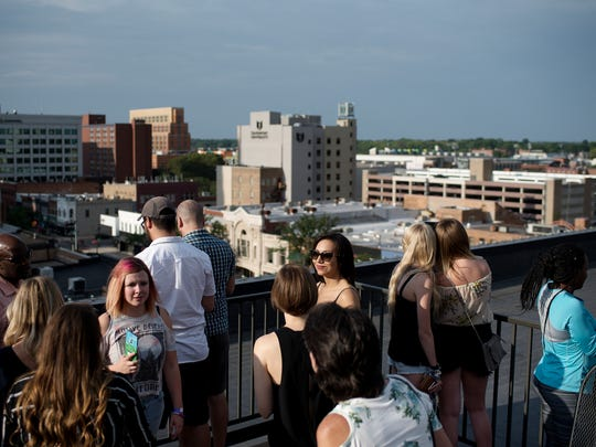 Guests mingle outside on the sixth floor of The Knapp's Centre during Lansing 5:01's Rooftop Hop on Thursday, July 12, 2018, in downtown Lansing. The event featured different activities, food and artists on the rooftops of four downtown building. Locations that hosted the festivities included La Fille Gallery, The Knapp's Centre, The Christman Building and Marketplace Apartments.