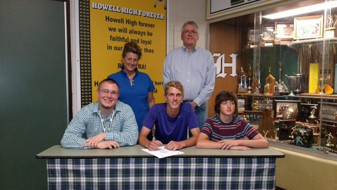 Dillon French, center, signs to play basketball next season at Albion College alongside Howell coach Nick Simon, bottom left, his brother Kip, bottom right, and his parents, Rick and Desiree, back.