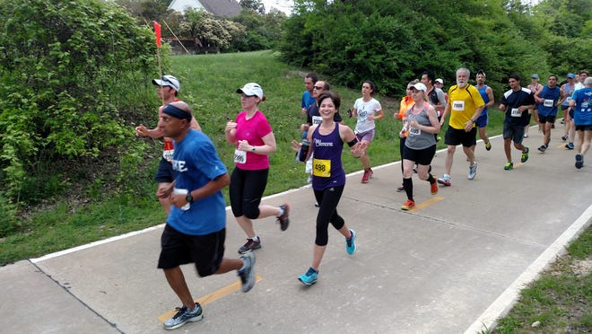 Education reporter Leigh Guidry (in purple) waves to her friends who caught her about halfway through her 10th half marathon on Sunday. The Big D Half Marathon route brought her through a park by White Rock Lake in Dallas, Texas.