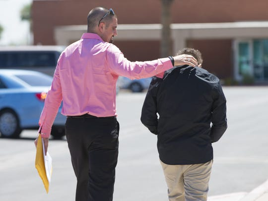 "Nick Dugas, 30, walks with his 14-year-old son, ""Bug"", after adoption proceedings at Durango Juvenile Court in Phoenix on June 8, 2018."