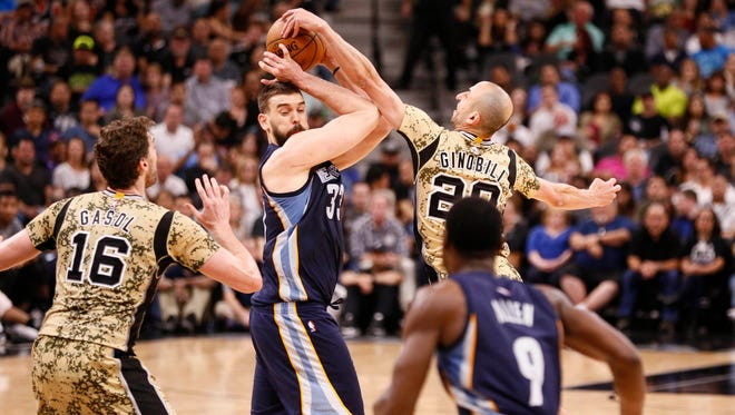 Mar 23, 2017; San Antonio, TX, USA; San Antonio Spurs shooting guard Manu Ginobili (20) tries to steal the ball from Memphis Grizzlies center Marc Gasol (33) during the second half at AT&T Center.