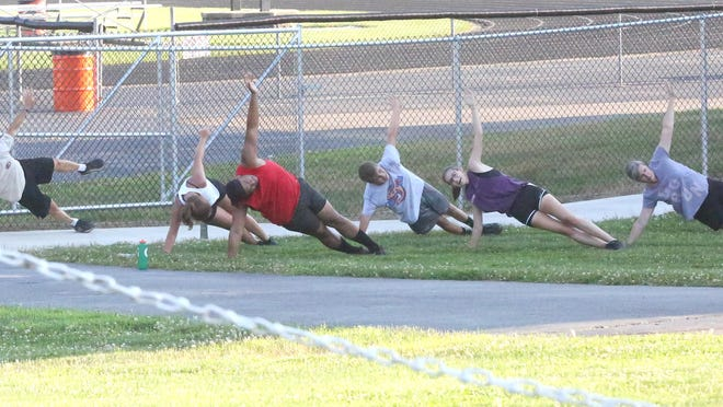 Participants in the Newcomerstown cross country program go through conditioning drills during a recent workout at the high school.