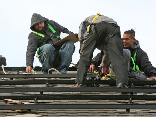 Members from Green Alternatives Inc., Edsel Koscielniak, from left, Malcolm Raman, and Brian Gonzalez install a solar panel system in Carmel, Tuesday, October 31, 2017.