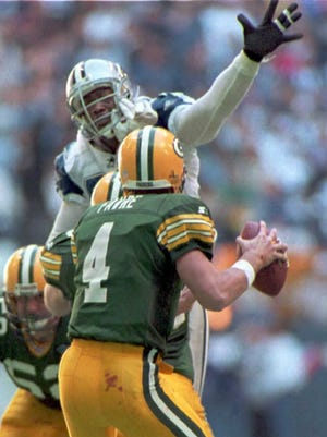 Green Bay Packers' quarterback Brett Favre is pressured by Dallas Cowboys' defensive end Charles Haley during the NFC divisional playoff game at Texas Stadium in Irving, Texas, in January 1995.
