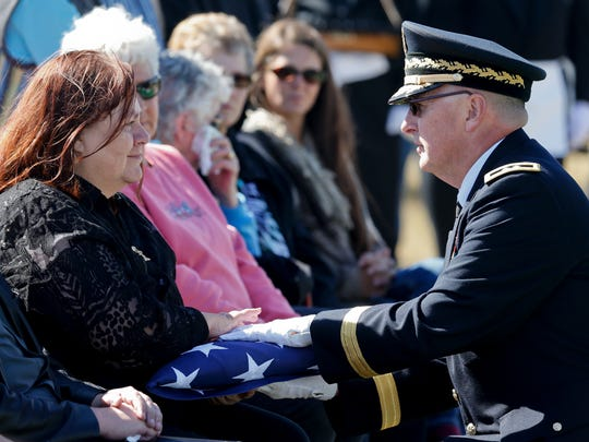 Maj. Gen. Matthew Quinn, adjunct general of Montana Army National Guard, hands Sandi Jones a U.S. flag that was draped over the coffin of her uncle, 1st Lt. William Bernier, during his burial ceremony.