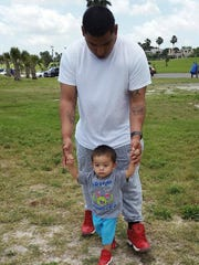 Gilbert Sierra III helps his son Gilbert Sierra walk at a park.