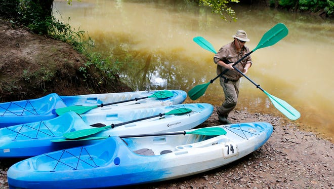 Collierville firefighter Johnny Campbell gets rental kayaks set for customers on a section of the Wolf River between Lagrange and Moscow, Tenn. State officials cited Norfolk Southern Railway for discharging pollution into a tributary of the Wolf River.