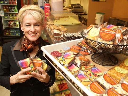 Alisa Shakespeare poses with a selection of her Total Cluster Fudge desserts and snacks at O'Connors Deli in Genoa Township, her first retail location. Now Shakespeare is expanding her product availability at retailers throughout the area.