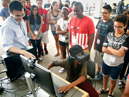 Ester Ubadigbo, 13, tries out the Oculus Rift with help from Register reporter Matt Patane at Tech Journey, a local organization to help kids connect and train with technology at Central Academy Tuesday, July 14, 2015.