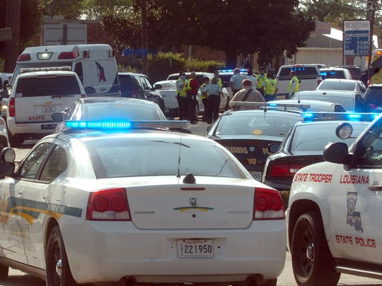 Squad cars and ambulances converge at Duffy and Napoleon Avenues in Sunset during a standoff with an armed suspect Wednesday.
