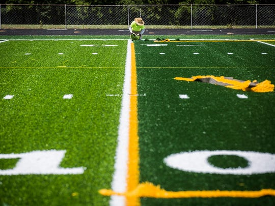 Workers with The Motz Group put the finishing touches on New Castle High School's turf football field Tuesday afternoon.