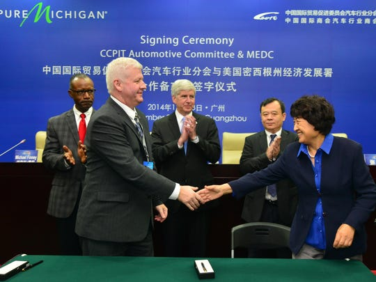 Former Michigan Economic Development Corporation President and CEO Mike Finney, left front, shakes hands after an agreement between the Michigan Auto Office and the Chinese Council for Promotion of International Trade Automotive Committee during the Guangzhou Auto Show. It was taken during the Governor's fourth trade mission to China in November, 2014.