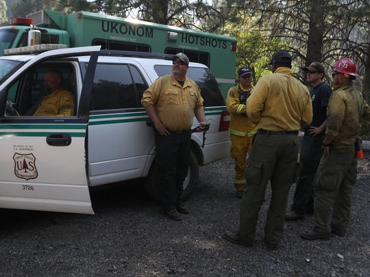 Fire officials monitor and make plans Tuesday at a fire burns west of Dunsmuir