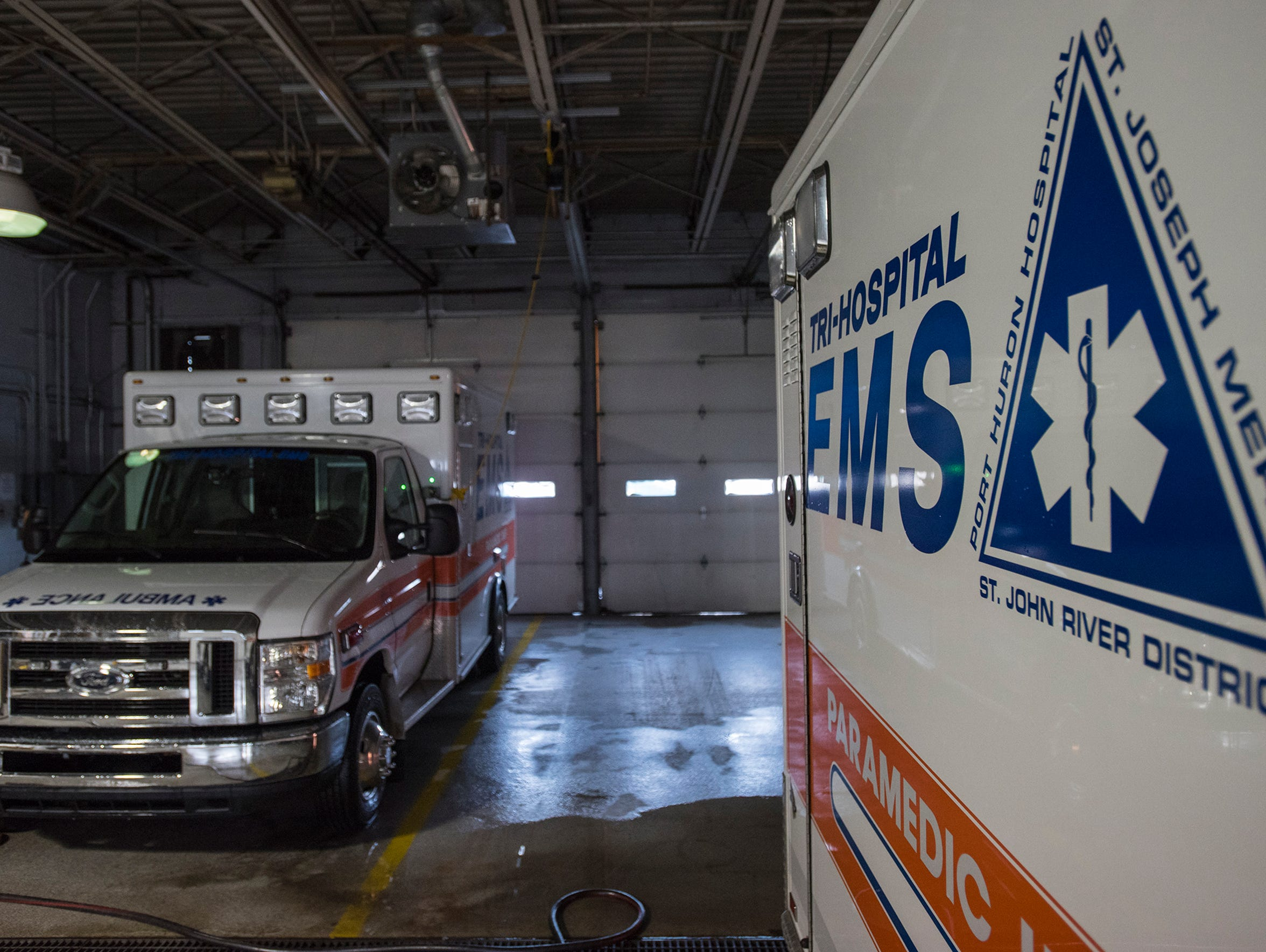 Two Tri-Hospital EMS ambulances are parked in the garage