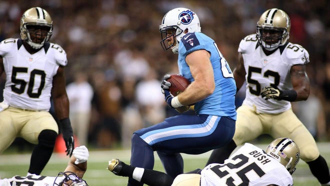 Titans tight end Taylor Thompson (84) is tripped up above Saints free safety Rafael Bush (25) in the first half Friday.