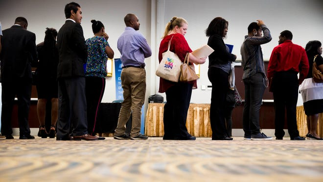 In this June 23, 2014 photo, job seekers wait in line to meet with recruiters during a job fair in Philadelphia.