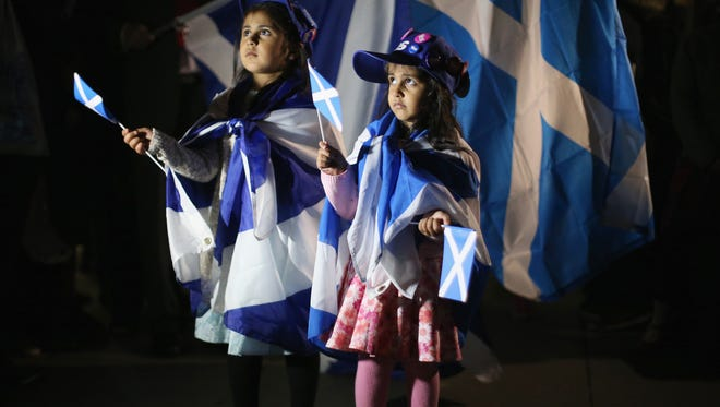 Two young girls join the crowds outside the Scottish Parliament in Edinburgh Thursday as Scotland voted on whether to remain part of the United Kingdom or become an independent country.