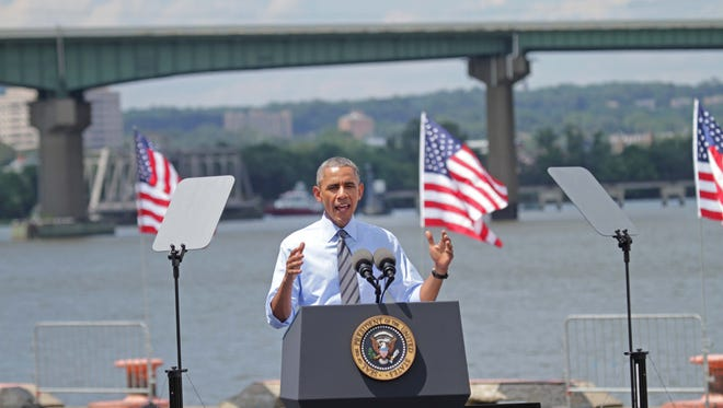 With the damaged I-495 bridge in the background, President Barack Obama announces a new plan to improve the nation's infrastructure at the Port of Wilmington on Thursday.