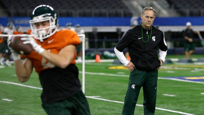 Michigan State coach Mark Dantonio, right, watches team practice for the Cotton Bowl against Alabama, Monday in Arlington, Texas.