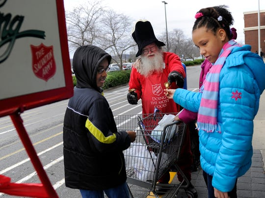 Gary Jackson lets Ellington and Indigo Flowers ring his Salvation Army bell as he collects donations outside the Franklin Wal-Mart on Tuesday.