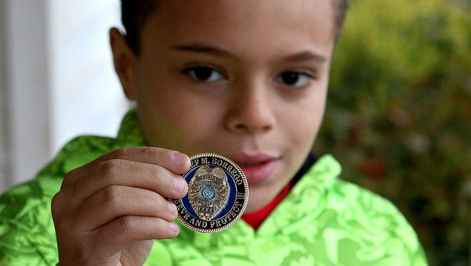 Thomas James holds up a special coin he received Thursday afternoon from Wichita Falls Police Chief Manuel Borrego. Borrego and Mayor Stephen Santellana stopped by his house to personally thank him for his role in saving a young girl from being kidnapped on Dec. 10.