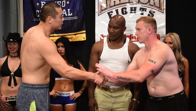 As former world heavyweight champion Evander Holyfield looks on, Chinese Heavyweight Zhang, left, and Curtis Lee Tate shake hands during Thursday's weigh-in at John Ascuaga's Nugget. The two will fight as part of the Rural Rumble card in Fallon on Friday night.