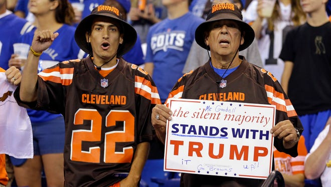 Cleveland Browns fans hold a sign following the national anthem to support President Donald Trump's criticism of NFL protests.